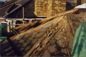Removing damaged slates and rotted timber from around the bay